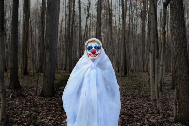 evil clown in a dark forest in a white veil