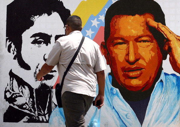 A man walks past a mural portraying the Venezuelan flag, President Hugo Chavez and South American liberator Simon Bolivar at the 23 de Enero neighbourhood, in Caracas on March 5, 2013. Venezuela plunged deeper into an uncertain future on Tuesday as cancer-stricken President Hugo Chavez took a turn for the worse, hit by a severe infection and breathing problems. Venezuelan Vice-President Nicolas Maduro expelled US Air Force Embassy attache David Del Monaco, giving him 24 hours to leave the country, accusing him of conspiracy. AFP PHOTO/Geraldo Caso        (Photo credit should read GERALDO CASO/AFP/Getty Images)