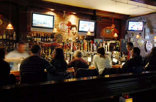 Patrons sit at the bar at the Downtown Bar and Grill in the